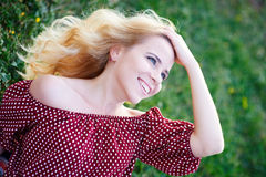 Happy smiling woman in a park on the grass Royalty Free Stock Images