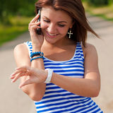Happy smiling woman on phone & checking time Royalty Free Stock Photos