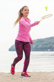 Happy smiling woman playing badminton at beach, active lifestyle Stock Photography