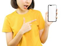 Happy smiling woman pointing with hand and finger to smart phone. royalty free stock images