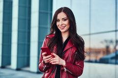 Happy smiling woman in red jacket is standing next to glass building and chating with someone by mobile phone.  royalty free stock photography
