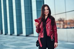 Happy smiling woman in red jacket is standing next to glass building and chating with someone by mobile phone.  royalty free stock image