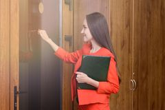 Happy smiling woman in a red suit with documents in hand knocking at the door to the boss Royalty Free Stock Images