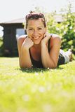 Happy Smiling Woman Relaxing on Grass Stock Images