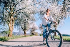 Happy smiling woman rides a bicycle on the country road under blossom trees. Spring is comming concept image royalty free stock image