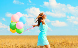 Happy smiling woman running with an air colorful balloons enjoying a summer day on field and blue sky background Royalty Free Stock Images
