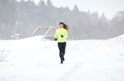 Happy smiling woman running outdoors in winter Stock Photos