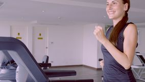 Happy smiling woman running on the treadmill in the gym In fitness center. royalty free stock photo