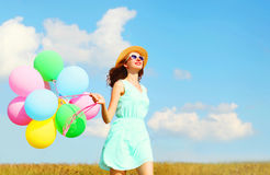 Happy smiling woman runs with an air colorful balloons is enjoying a summer day on meadow blue sky. Happy smiling woman runs with an air colorful balloons is Royalty Free Stock Photo