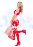 Happy smiling woman in santa claus clothes with bags Royalty Free Stock Image