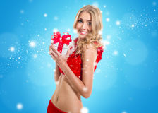 Happy smiling woman in santa claus clothes with present box. Con Royalty Free Stock Images