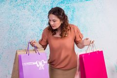 Woman at shopping holding colourful paper bags, packages. Happy smiling woman at shopping holding colourful paper bags in both hands royalty free stock photo