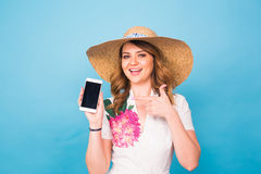 Happy smiling woman showing cell phone with black screen and gesturing thumb up, on a blue background.  Royalty Free Stock Image