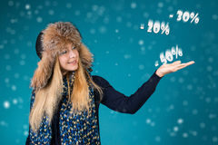 Happy smiling woman showing pointing on discounts 50%, 30%, 20%. Winter sale concept.