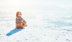 Happy smiling woman sits on the snowy mountain hill over the cit stock images