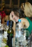 Happy smiling woman sitting at a bar counter Royalty Free Stock Images