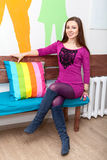 Happy smiling woman sitting on bench in room Royalty Free Stock Photos