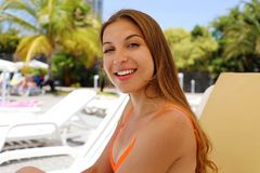 Happy smiling woman sitting on deck chair in tropical pool. Laughing girl enjoying the sun on holidays at hotel resort beach while. Looking at camera royalty free stock images