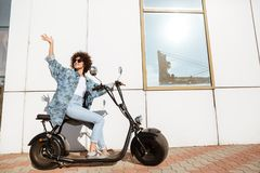 Happy smiling woman sitting on a modern motorbike Royalty Free Stock Image