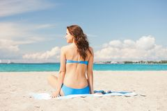 Happy smiling woman sitting on a towel Stock Photo
