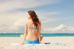 Happy smiling woman sitting on a towel Stock Images