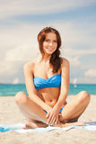 Happy smiling woman sitting on a towel Royalty Free Stock Photography