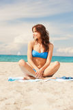 Happy smiling woman sitting on a towel Royalty Free Stock Photo