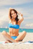 Happy smiling woman sitting on a towel Royalty Free Stock Images