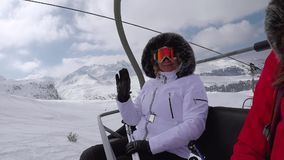 Skier Climbs Up The Chair Lift To The Mountain Top And Wave Her Hand In Greeting. Happy smiling woman skier or snowboarder climbs up the mountain sitting in the stock footage