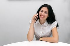 Happy smiling woman with smartphone. Portrait of attractive cheerful girl talking on cellphone and laughing. Lovely brunette sitting at white desktop and looking royalty free stock photography