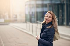 Happy smiling woman standing in the wind on an urban street. With her long blond hair blowing around her face with lateral copy space royalty free stock image
