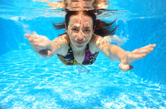 Happy smiling woman swims underwater in pool Stock Image