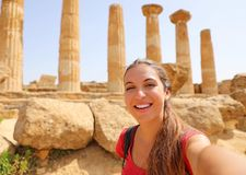 Happy smiling woman taking self portrait with greek temple on the background in the Valley of the Temples at Agrigento, Italy stock photography