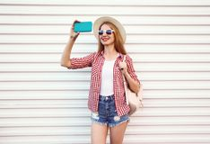 Happy smiling woman taking selfie picture by phone in summer round straw hat, checkered shirt, shorts on white wall royalty free stock photos