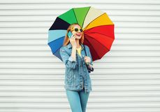 Happy smiling woman talks on smartphone holds colorful umbrella. On white background in city stock images