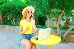 Happy smiling woman talks on smartphone, laptop computer Royalty Free Stock Photography