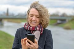 Happy Smiling woman texting on her mobile phone royalty free stock photography