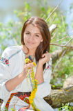 Happy smiling woman in traditional Ukrainian dress making flower garland Royalty Free Stock Image