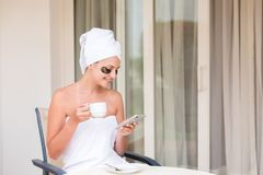 Happy smiling woman in under-eye patches readind sms message and drinking coffee at hotel terrace resort. morning holiday concept royalty free stock photography
