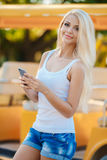 Happy smiling woman using her phone in the city Royalty Free Stock Photos