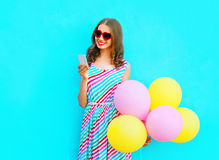 Happy smiling woman using smartphone holding an air colorful balloons. On a blue background Stock Images