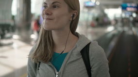 Happy smiling woman using travolator in airport terminal. Using her smartphone, listening to music stock video footage