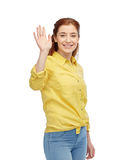 Happy smiling woman waving hand over white. People, and gesture concept - happy smiling young woman waving hand over white Royalty Free Stock Image