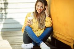 Happy smiling woman is wearing yellow sweater drinking coffee near old retro bus. Portrait of happy smiling girl is wearing yellow knitted sweater and jeans is Stock Photography