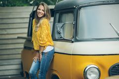 Happy smiling woman is wearing yellow sweater near old retro bus Royalty Free Stock Photos