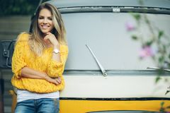 Happy smiling woman is wearing yellow sweater near old retro bus Royalty Free Stock Image