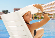 Happy smiling woman in white hat near the pool Stock Photo