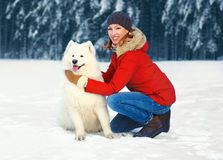Happy smiling woman with white Samoyed dog on snow walking in winter Stock Images
