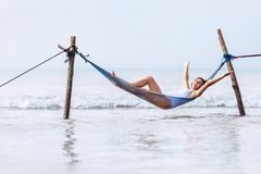 Happy smiling woman in white swimsuit lies in hammock swing over. The ocean surf line Royalty Free Stock Photography