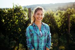 Woman winemaker with grapes in a vineyard. Happy smiling woman winemaker with grapes in a vineyard stock image
